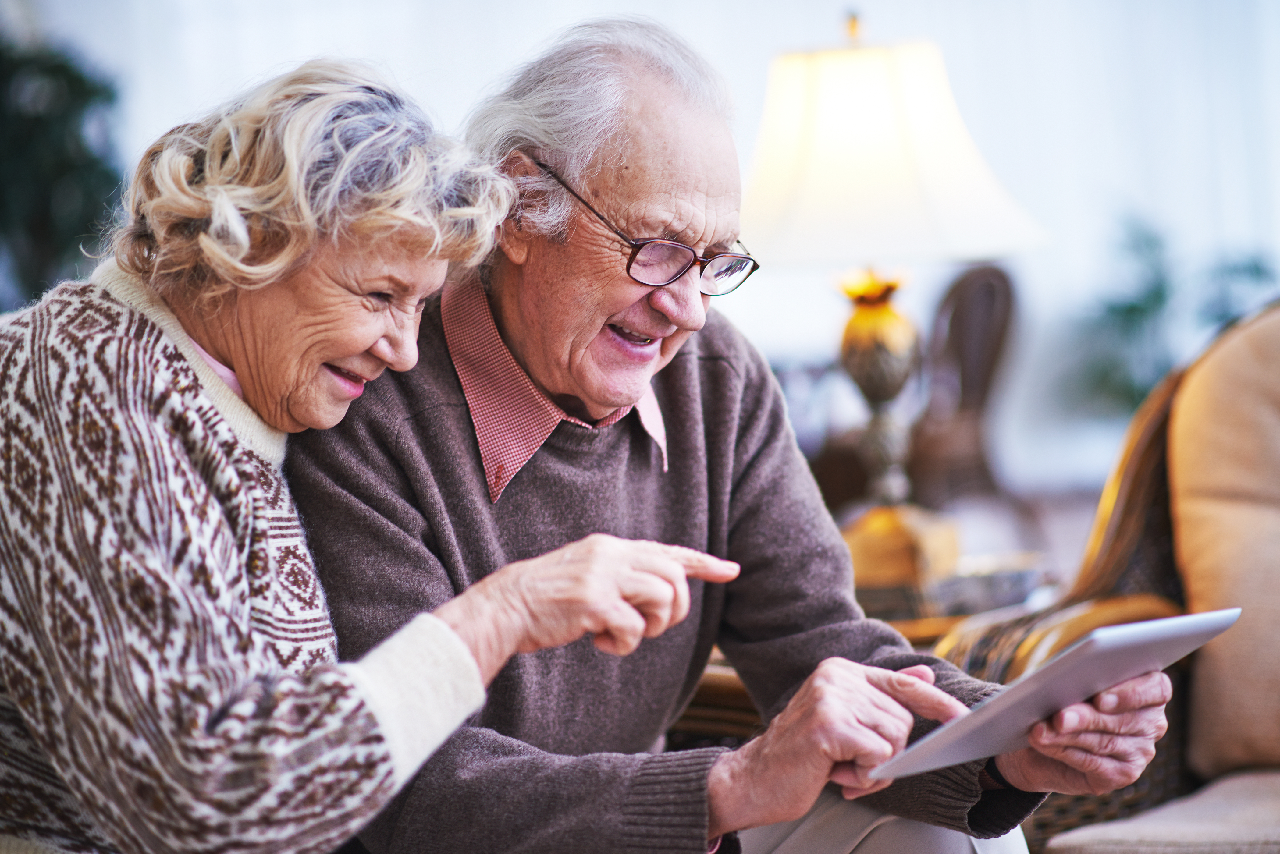 An older couple using a tablet device at home