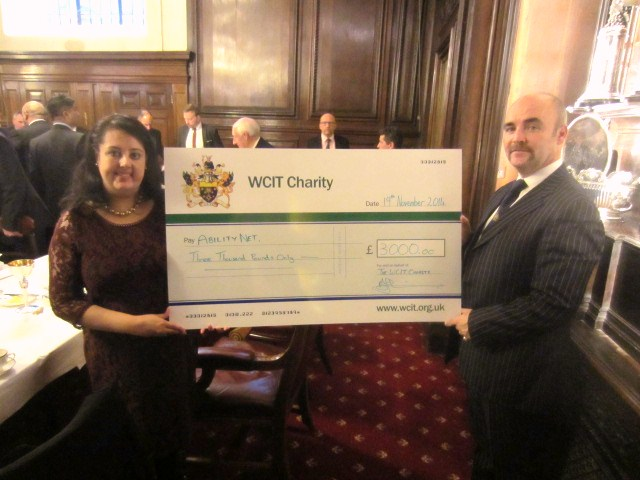 AbilityNet Trustee Nishita Sharma receives a large cheque from Mr Alan O'Connor who is Beadle for the Worshipful Company