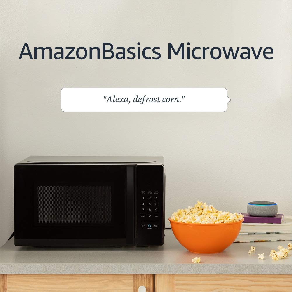 Photo of the Alexa microwave on a kitchen counter next to a bowl of popcorn