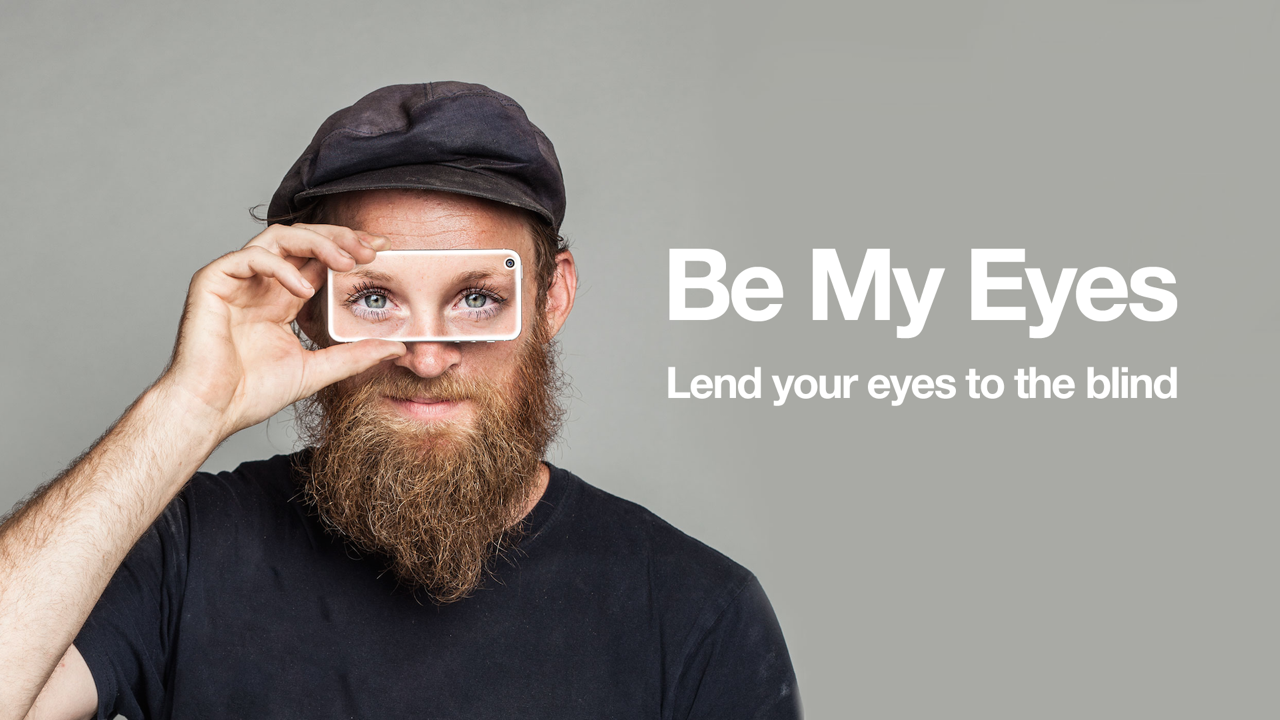 Photo of a man holding up a smartphone to his eyes with an image of someone else's eyes on the phone display. Be My Eyes, lend your eyes to the blind strapline