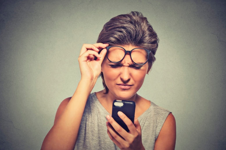 A woman lifting her glasses off her face, struggling to read something on her phone