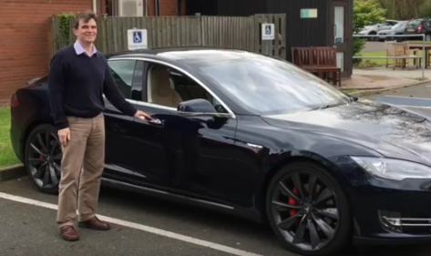 Robin standing next to a Tesla that he used for a test 'drive'