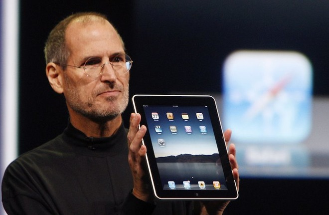 Steve Jobs holding up an iPad