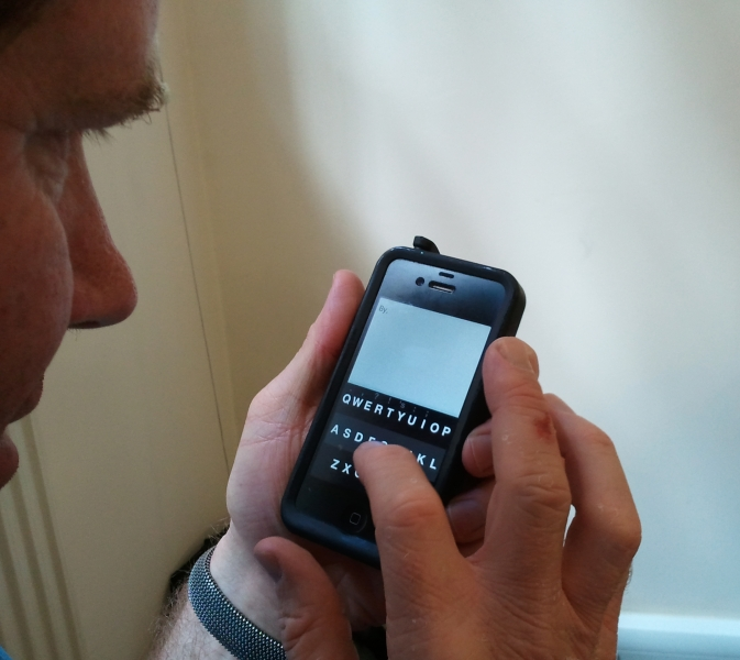 Photo of Rory holding up his iphone, showing the fleksy keyboard in action