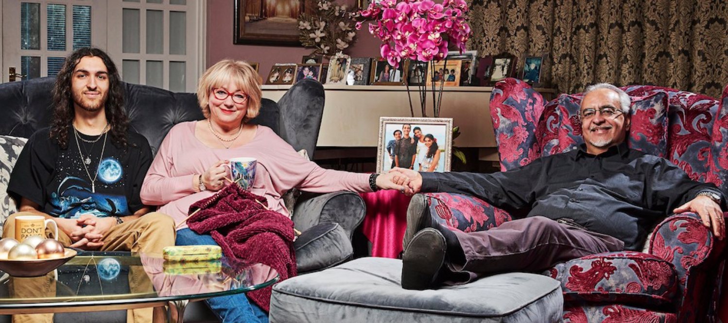 older man and woman and younger man look happy sitting on sofa in colourful lounge