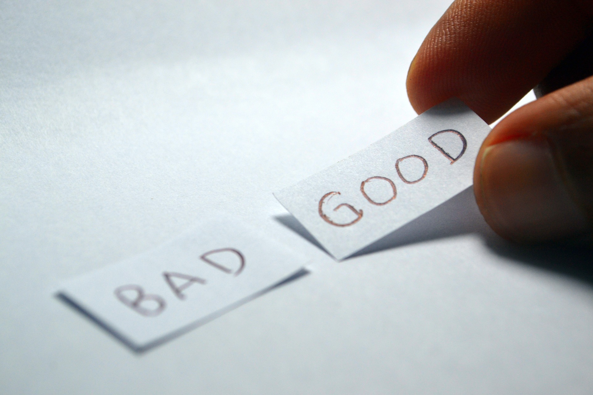 image: 2 pieces of paper saying bad and good. A hand is picking up the one that says good