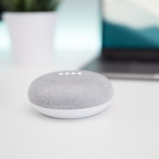 A Google Home Mini speaker on a white surface