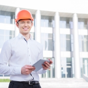 builder with tablet looking happy and confident