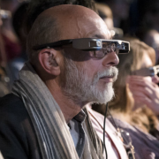close up of man in sixties wearing smart caption glasses at theatre