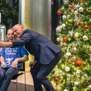 Lost Voice guy on stage at Barclays HQ with Mark Walker AbilityNet, Christmas tree in background