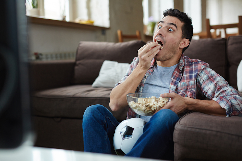 Man eating popcorn in front of TV looking surprised
