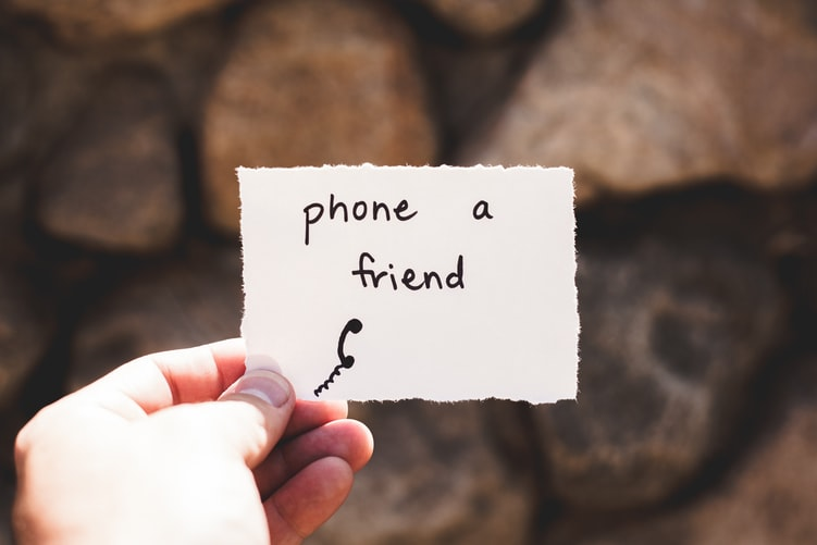 Shows a hand holding a piece of paper. On it are the words 'phone a friend'.
