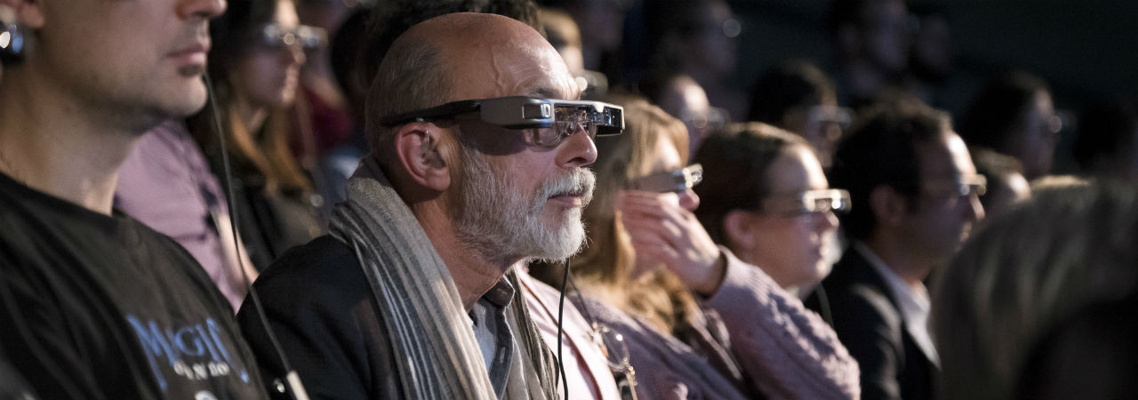man in theatre audience wearing smart caption classes