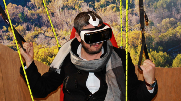 man wearing VR glasses in simulated mountain scene
