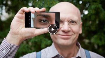 Man smiling holding camera phone to his eye