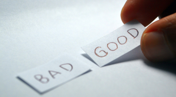 Two pieces of paper with good and bad written on them, the hand is picking up the good piece of paper