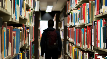 A student walking through a library out of focus