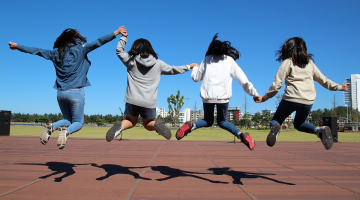 4 students jumping in a field