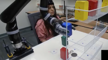 someone wearing a brain cap controlling a robotic arm