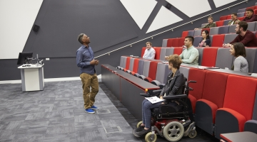 student in wheelchair in university lecture hall